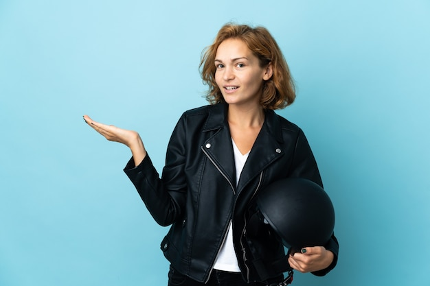 Georgian girl holding a motorcycle helmet isolated on blue background extending hands to the side for inviting to come