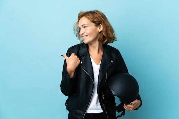 Georgian girl holding a motorcycle helmet isolated on blue background pointing to the side to present a product