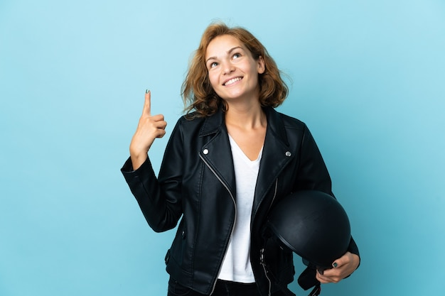 Georgian girl holding a motorcycle helmet isolated on blue background pointing up a great idea