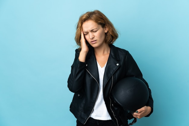 Georgian girl holding a motorcycle helmet isolated on blue background with headache