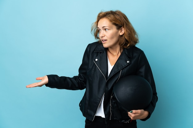 Georgian girl holding a motorcycle helmet isolated on blue background with surprise expression while looking side