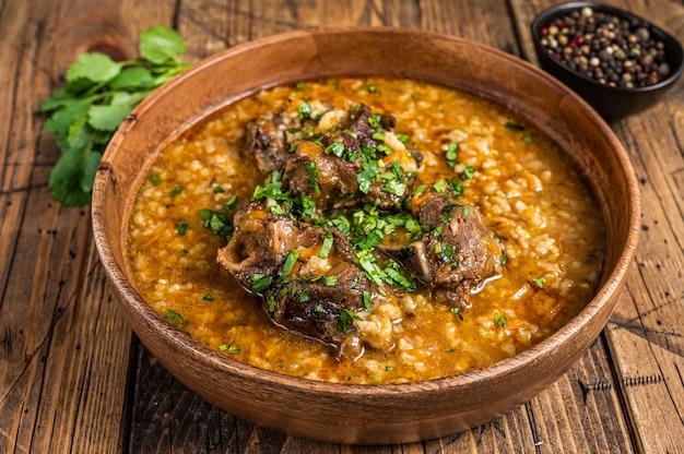 Грузинский суп из баранины харчо с рисом, помидорами и специями в деревянной миске. деревянный