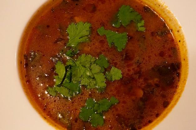 グルジアのハルチョースープ、おいしい国の料理。テーブルの上の白いプレートに牛肉または子羊のスパイシーなトマトスープ、クローズアップ