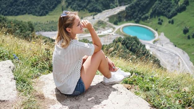 Военно-грузинская дорога, россия памятник дружбы с грузией. смотровая площадка искусственного озера. сидит девушка в шортах в горах. поход в горы, отдых на лугу, на природе