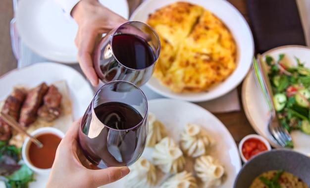 Грузинская ресторанная еда на столе, вино в руках Premium Фотографии