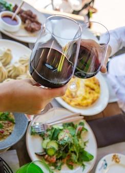 Грузинская ресторанная еда на столе, вино в руках