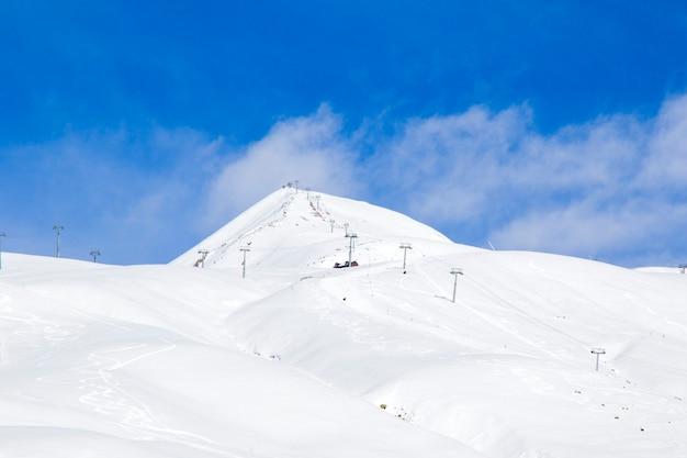 Georgian ski resort in gudauri. snowy mountains, daytime and sunlight.