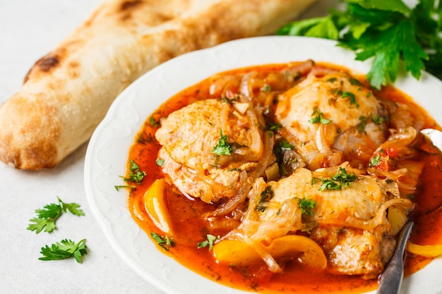 Georgian traditional chicken chakhokhbili in a white plate.