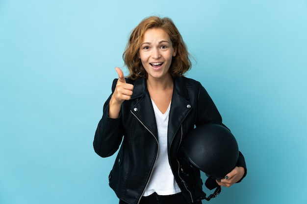 青い壁に分離されたオートバイのヘルメットを保持しているジョージ王朝の女性は驚いて正面を指しています