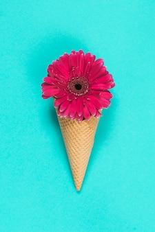 Цветок герберы в вафельном рожке на столе