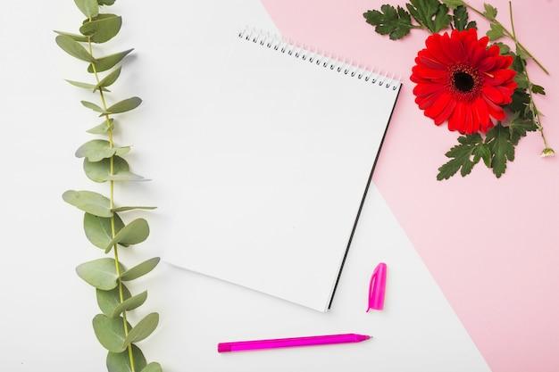 ガーベラ花;小枝;螺旋状のメモ帳とデュアル背景のペン