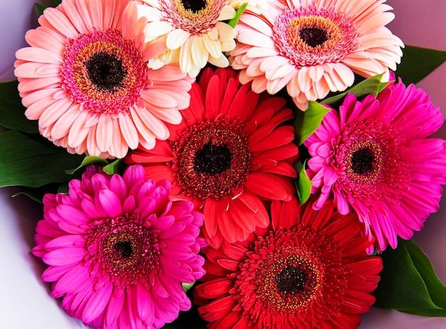 Букет цветов герберы. цветочный стол. красные, желтые, розовые цветочные головки