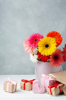 Gerbera flowers in a bucket with gifts