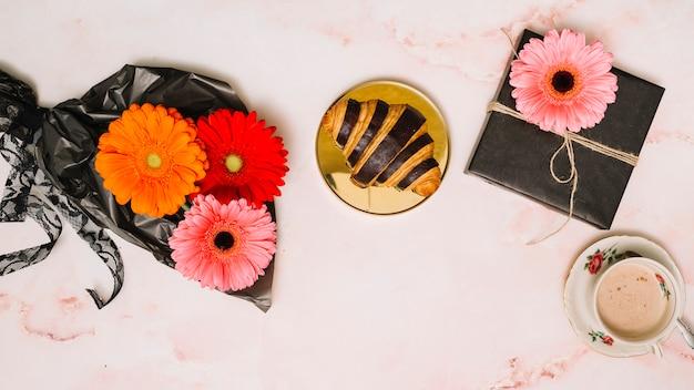 Цветы герберы на упаковочной пленке с подарочной коробкой и круассаном