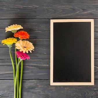 나무 테이블에 빈 칠판과 거 베라 꽃