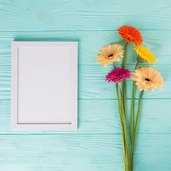Цветы герберы с пустой рамкой на столе