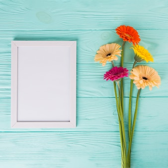 Gerbera flowers with blank frame on table