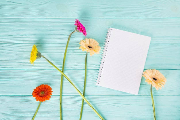 Gerbera flowers with blank notebook on table