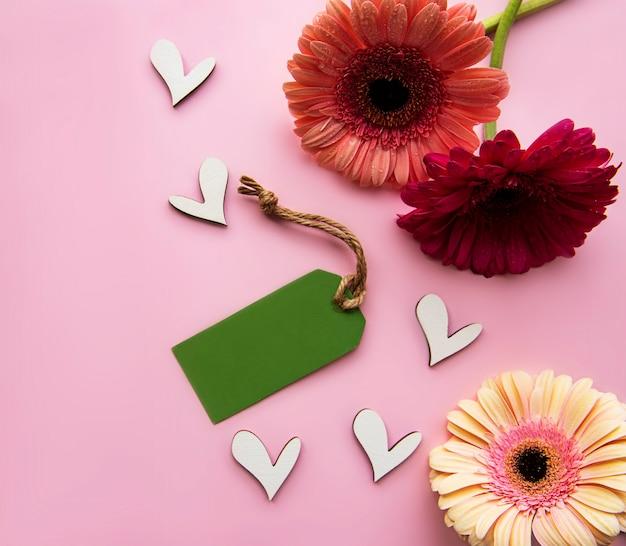 Gerbera 꽃, 나무 하트와 핑크 파스텔에 녹색 종이 태그. 평면도