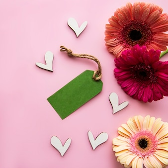 Gerbera  flowers wooden hearts and green paper tag on a pink pastel background top view