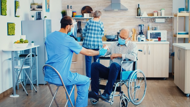Geriatrician giving pills to elderly disabled patient in wheelchair during coronavirus home visit. male nurse social worker at senior handicapped couple with disability explaining covid-19 spreading