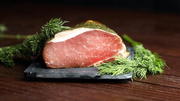 Герки из свинины со специями и свежим зеленым тимьяном на сланцевой разделочной доске на деревянном столе