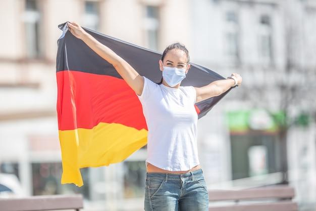 마스크를 쓴 독일 팬이 야외에서 깃발을 들고 웃고 있다.