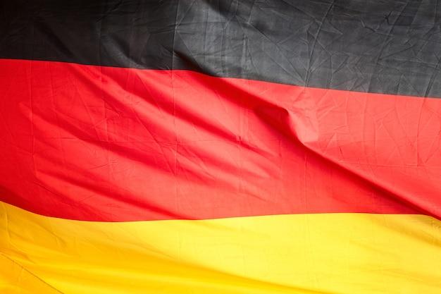 독일 국기입니다. 물결 모양의 검정, 빨강, 금색 패브릭 배경