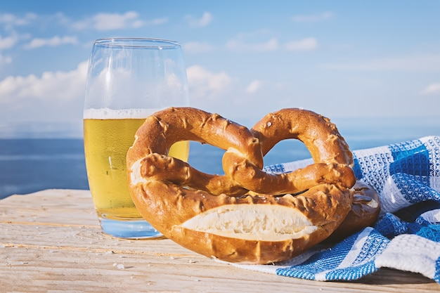 German pretzel and glass of beer in sunlight aginst blue sky