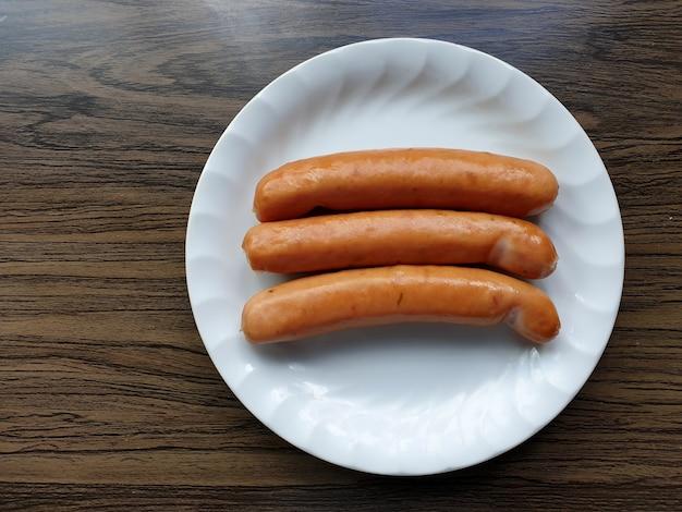 나무 배경에 흰색 접시에 독일 소시지