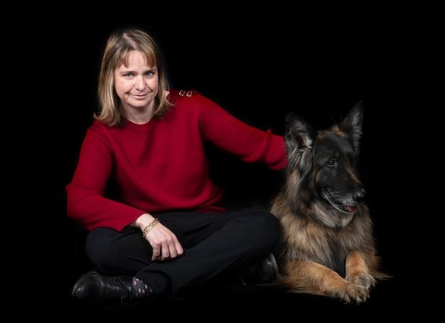 Немецкая овчарка и женщина на черном фоне