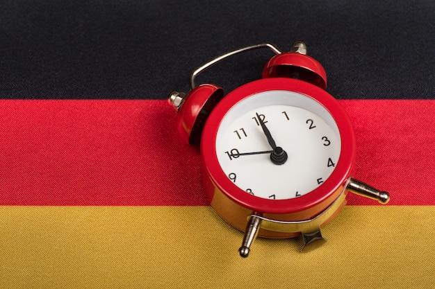 ドイツの旗とビンテージの目覚まし時計をクローズアップ