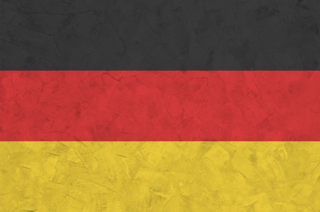 Germany flag depicted in bright paint colors on old relief plastering wall. textured banner on rough background