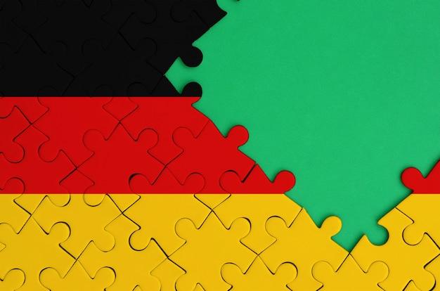 독일 국기는 오른쪽에 무료 녹색 복사 공간이있는 완성 된 직소 퍼즐에 그려져 있습니다.