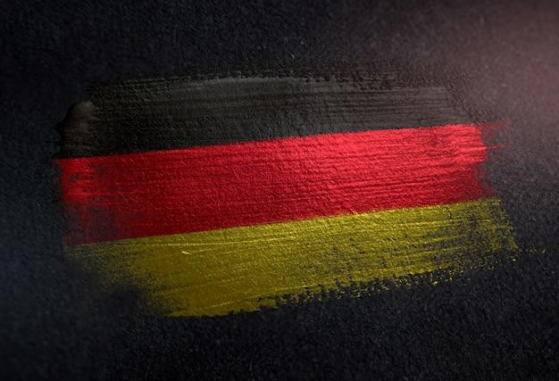 Germany flag made of metallic brush paint on grunge dark wall