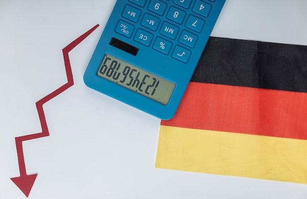 Germany flag with red fall arrow and calculator. fall graph going down. economic recession, crisis