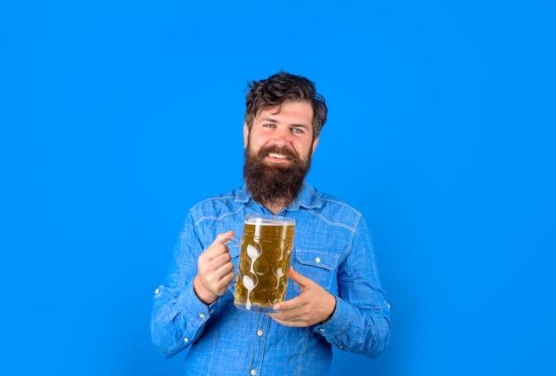 Мужчина по традициям германии держит чашку пива с пеной для пива октоберфест в стекле стильный мужчина