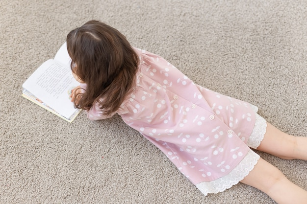 Gesign, baby, people concept - young girl lying on the floor and reading a book.
