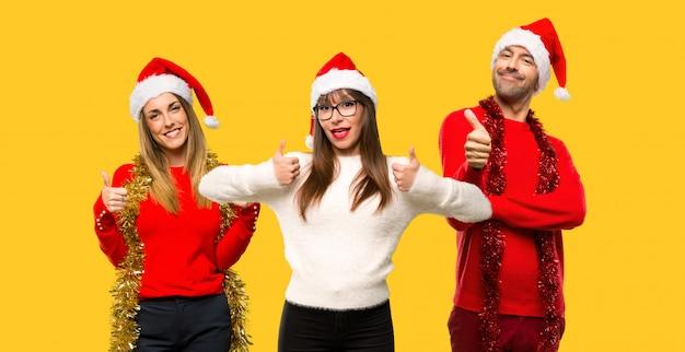 人々のグループブロンドの女性は、お祝いのgesturを与えるクリスマス休暇のために身に着けている