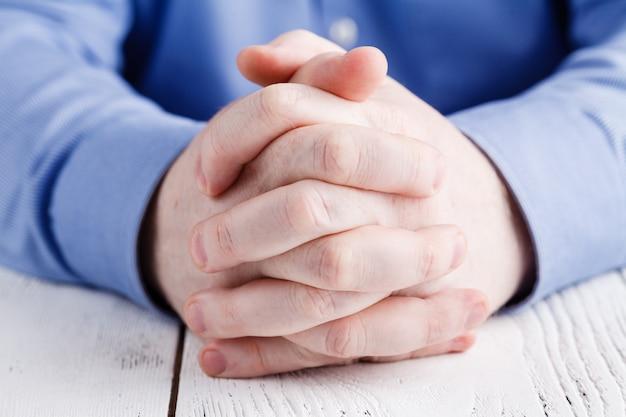 Жест и люди концепции - закрыть руки старшего человека на столе