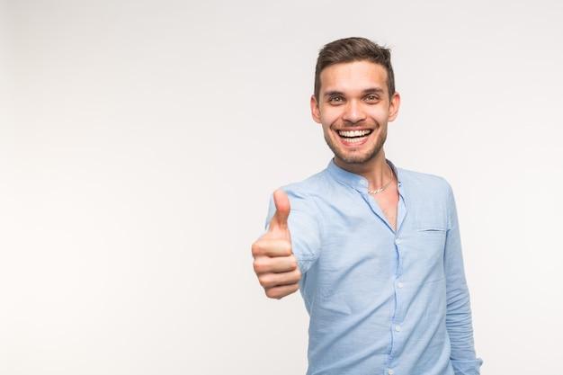 Концепция жеста и людей - красивый человек с улыбкой показывая большой палец вверх на белой стене с космосом экземпляра.