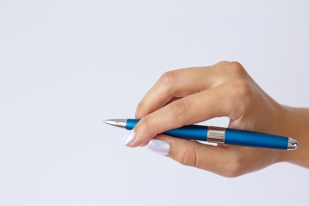 ジェスチャーとサイン、白い壁に金属の青いペンを持っている女性の手