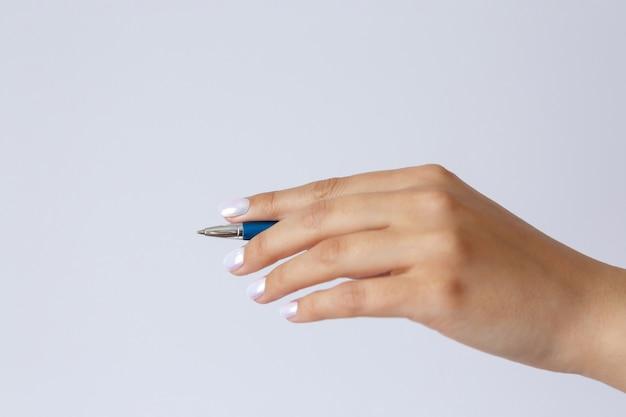 金属ペンを持っている女性の手のジェスチャーとサイン