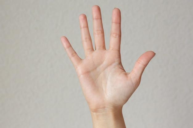 Жест и знак, женская рука показывает стоп на свету