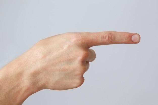 제스처 및 기호, 흰 벽에 남성 손. 보여주는 손가락