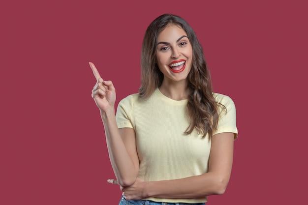 ジェスチャー、注意。長いウェーブのかかった髪と唇に手を上げて人差し指に真っ赤な口紅を持つ幸せな若い美しい女性