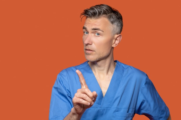 Gesture, attention. serious happy man in blue medical suit calling for attention on orange background