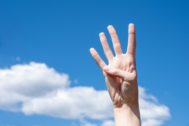 Gesture closeup of a woman's hand showing four fingers, isolated on a background of blue sky with clouds, sign language symbol number four.