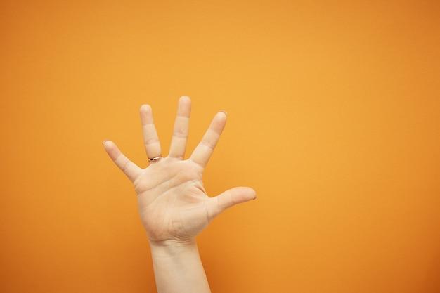 Жест, женская рука показывает пять пальцев, изолированных на оранжевом.