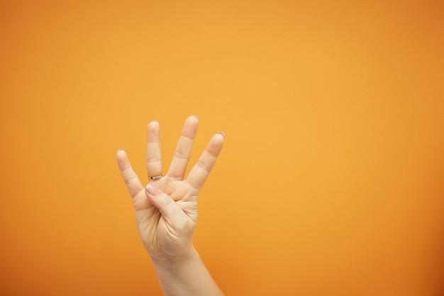 Жест, женская рука показывает четыре пальца, изолированные на оранжевом.